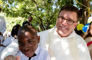 Boy waits with priest during baptism for children abandon during 2010 earthquake in Haiti